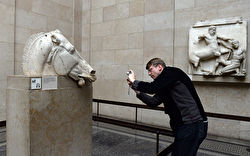 Photo of a man taking a photo of one of the Elgin marbles