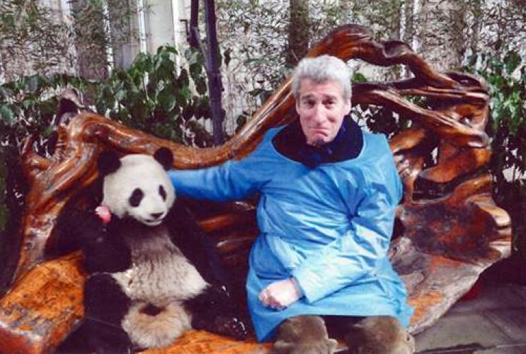 Photo of Jeremy Paxman sitting with a young panda