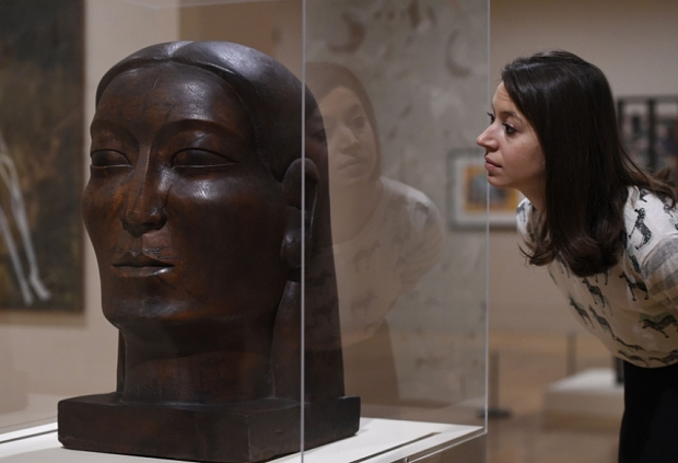 A photo of a woman looking at a sculpture of a head